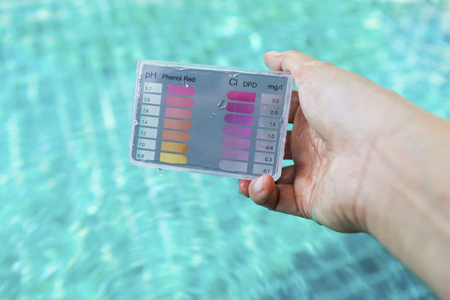 balanza de laboratorio: Girl hand holding water testing test kit over clear swimming pool water background