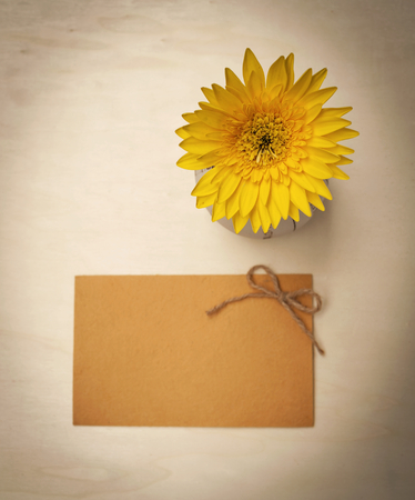 writ: Yellow daisy flower and blank yellow paper card on wood background