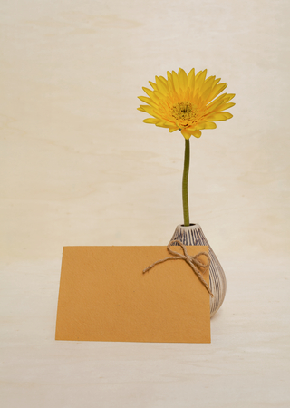writ: Yellow daisy in ceramic vase and yellow paper card on wood background Stock Photo