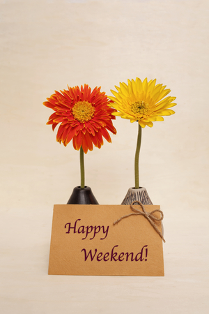 writ: Happy weekend on yellow paper card and daisy flower Stock Photo