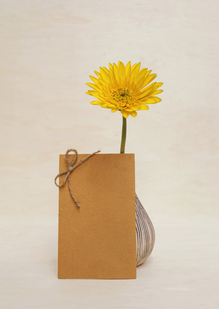 writ: Yellow flower and paper card on wood background