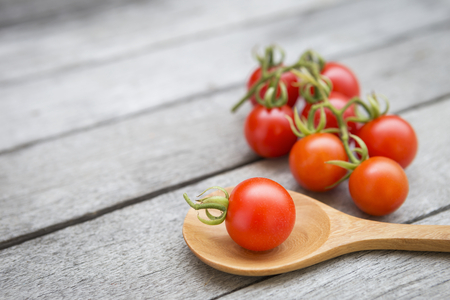 Closeup fresh tomato on wooden spoon over old wooden floor background Stock Photo