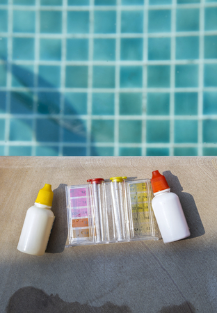 Liquid water testing test kit with space on swimming pool, outdoor day light