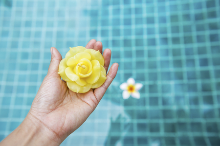swimming candles: Beautiful yellow rose candle flower on girl hand over blurred blue swimming pool water background, spa concept, outdoor day light Stock Photo