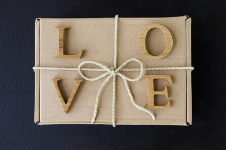 storage box: Love letter on brow gift box with paper string ribbon over black background, valentine gift