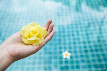 swimming candles: Beautiful yellow rose candle in girl hand over blurred blue swimming pool background, spa decoration concept