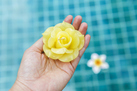 swimming candles: Yellow rose candle flower in girl hand over blurred blue swimming pool background, outdoor day light