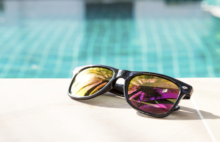 Summer concept, polaroid sunglasses on swimming pool edge, outdoor day light