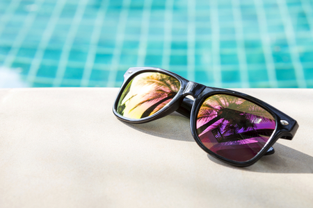 Design sunglasses on swimming pool edge, summer concept background, outdoor day light