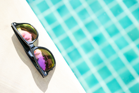 Summer concept background of design sunglasses on swimming pool edge, sunny outdoor day light