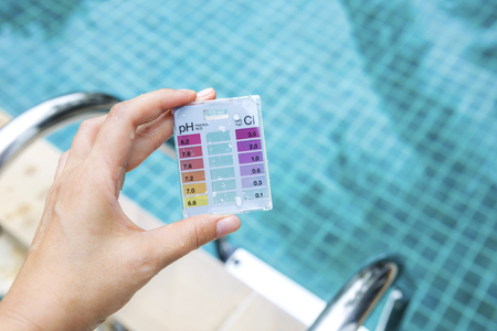 Girl hand holding mini water testing test kit over blurred swimming pool background, outdoor day light Banco de Imagens