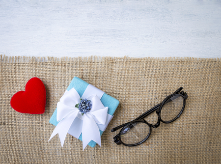 Gift box and red heart with eyeglasses on hessian texture background