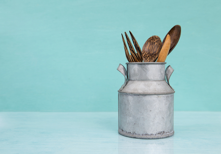 Wooden spoon in vintage metal can on blue background Stock Photo
