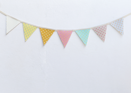 Design vintage fabric party flag over white cement wall texture background, outdoor day light