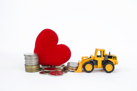 cargador frontal: Yellow front loader moving stack of coins with pile of coins and red heart on backgrund, business & financial concept