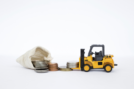 Yellow forklift truck lifting coins with pile of coins in canvas bag, business concept