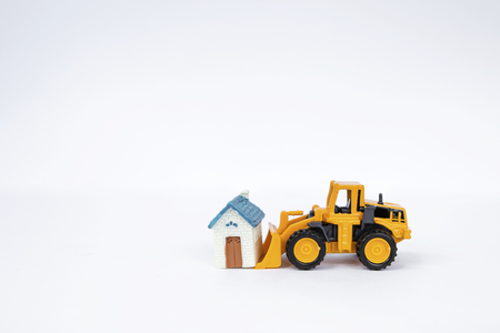 cargador frontal: Front loader truck moving miniature house on white background, real estate and property business concept