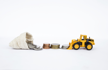 Front loader truck moving coins into canvas money bag on white background, Banking and financial concept
