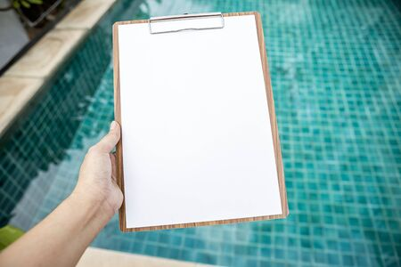 Blank white paper on wooden clipboard over blurred swimming pool background, pool check list