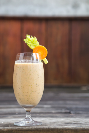 is green: Mixed fresh fruits and vegetables smoothie with space on wood background