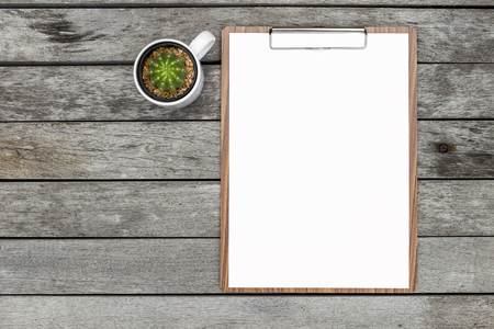 white sheet: Blank white paper on wooden paper clipboard with cactus cup on old wooden floor background