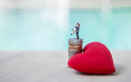 Happy couple standing on coin stack with red heart over blurred background