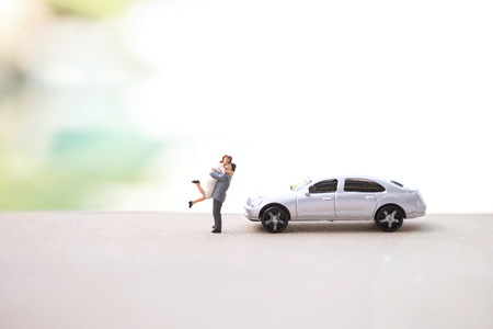 Happy miniature couple with new car over blurred background, outdoor day light Stockfoto