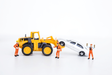 Car insurance business concept, miniature worker with front loader truck moving car
