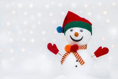 Design handmade snow man on white snow over blurred light bokeh on white background