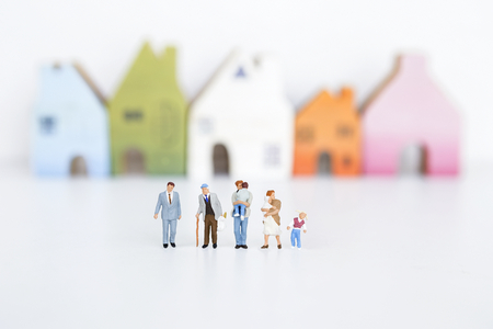 Miniature group of different kind of people over blurred house on white background