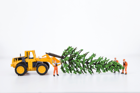 Miniature worker moving model tree and front loader truck on white background