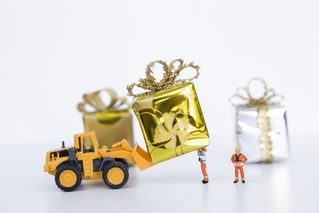 Miniature worker and yellow truck moving gift on white background