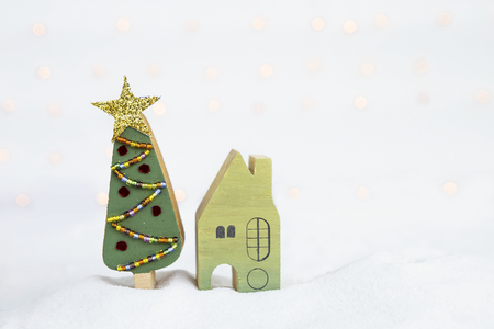 Miniature green wooden house and handmade wooden Christmas tree on white snow over blurred light bokeh on white background Stock Photo