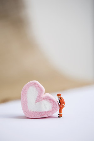 Miniature worker movie pink heart shape marshmallow over blurred background, love and valentine concept background