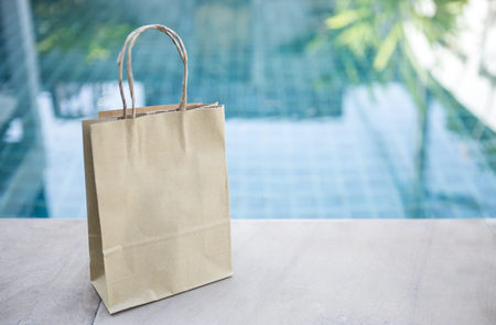 Brown paper shopping bag over blurred blue swimming pool water..