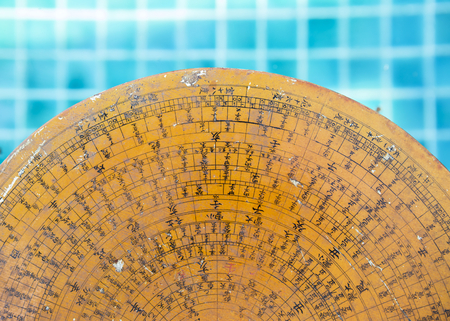 Old ancient Chinese wooden feng shui compass over blurred blue water background Stock Photo
