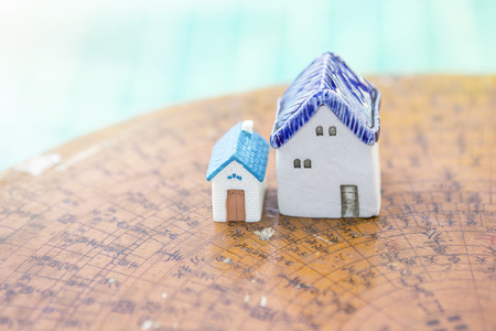 Miniature house design on wooden Chinese compass plate over blurred blue water background, property business concept