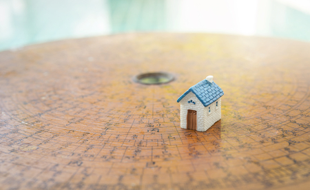 New miniature house on antique chinese compass over blurred background with morning light