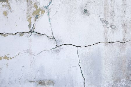 Abstract crack pattern on old white concrete wall background, construction problem concept