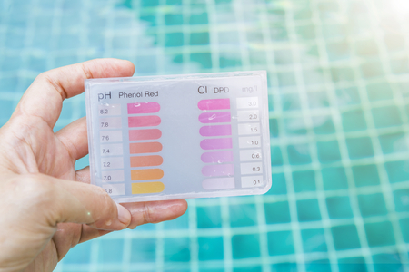 Girl hand holding water testing test kit over blurred blue swimming pool water background, healthy water treatment equipment check kit, summer outdoor day light