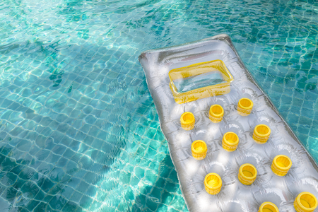 Inflatable sun lounger, swimming pool air bed mattress floating on clear water, comfortable pool float