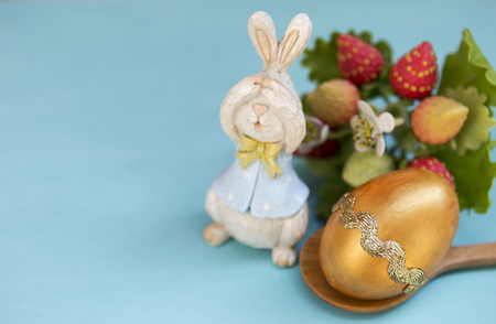 Happy Easter concept, cute wooden rabbit with gold design Easter egg on blue background