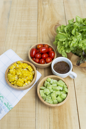Healthy food concept, fresh vegetable salad in wooden bowl with space on wooded table background