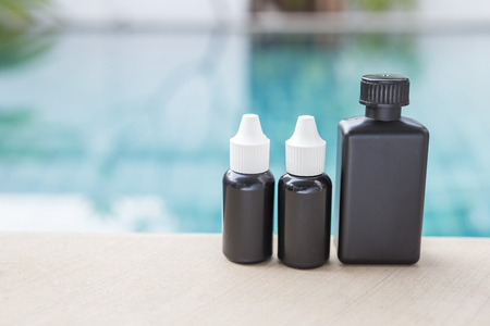 Black plastic container in different shape over blurred swimming pool background, outdoor day light, chemical bottle Stock Photo