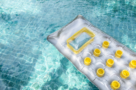New air mattress floating on clear swimming pool water, summer concept, outdoor day light Stock Photo
