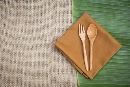 Wooden fork and spoon design on brow napkin over fresh green banana leaf and hessian fabric background