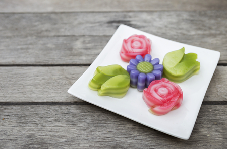 Colorful Thai style layer cake in flower shape on wood table background