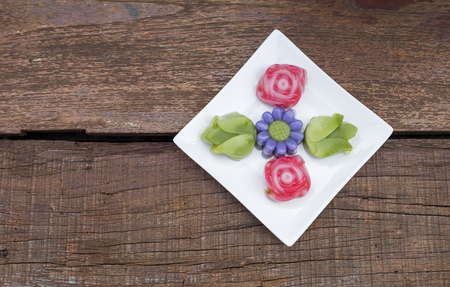 Colorful Thai layer cake design in different flower shape on white plate over old wooden table background Stock Photo