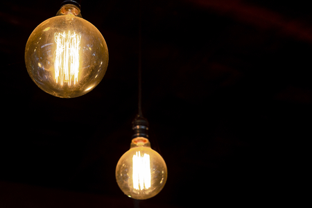 Vintage round tungsten filament bulb with dark background, technology and energy concept 写真素材