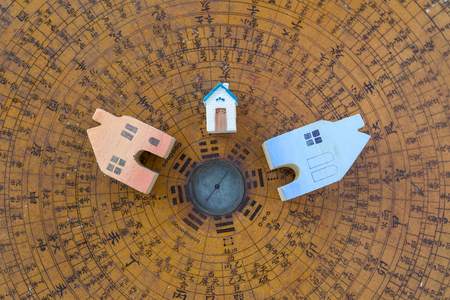 Wooden color miniature house design on ancient wooden Chinese compass background, house and property business concept Standard-Bild